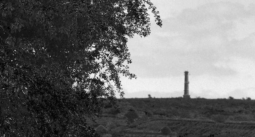 The Mine stack atop Kit Hill on the Horizon as seen from Kelly Bray framed by dark trees