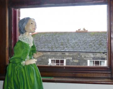 Nellie Sloggett looks out of a window at the new hoersemen on a rooftop