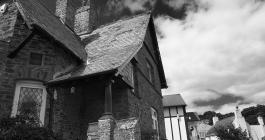 monochrome image of Gothic influenced cottage with dramatic sky behind