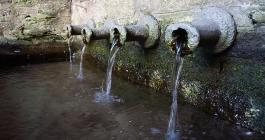 water spills out of the pipes of the pipewell
